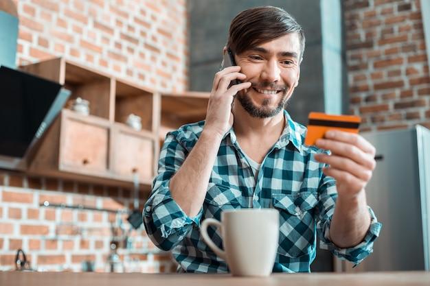 Freudiger kluger positiver mann, der am telefon spricht und lächelt, während er seine kreditkarte betrachtet