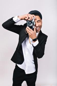 Freudiger lächelnder kerl im hut, anzug, der foto vor der kamera macht, spaß hat. modischer mann, fotograf, glücklicher tourist, schönes hobby, freizeit, aufgeregte person, glück.