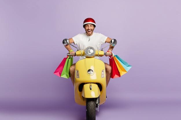 Freudiger lächelnder kerl mit helm und einkaufstaschen, die gelben roller fahren