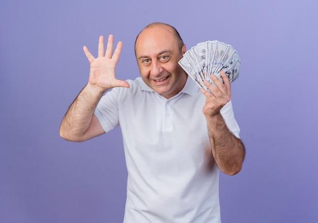 Freudiger lässiger reifer geschäftsmann, der geld hält und fünf mit hand lokalisiert auf lila hintergrund mit kopienraum zeigt