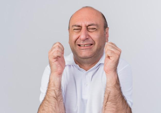 Freudiger lässiger reifer geschäftsmann, der ja geste mit geschlossenen augen tut, die auf weißem hintergrund lokalisiert werden