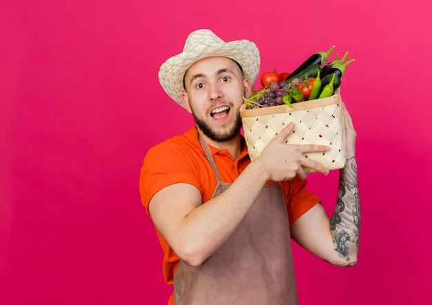 Freudiger männlicher gärtner, der gartenhut trägt, hält gemüsekorb auf schulter