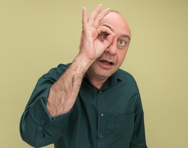 Freudiger mann mittleren alters, der grünes t-shirt trägt, das blickgeste lokalisiert auf olivgrüner wand zeigt