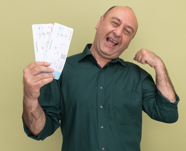 Freudiger mann mittleren alters, der grünes t-shirt trägt, das karten hält, die starke geste lokalisiert auf olivgrüner wand zeigen
