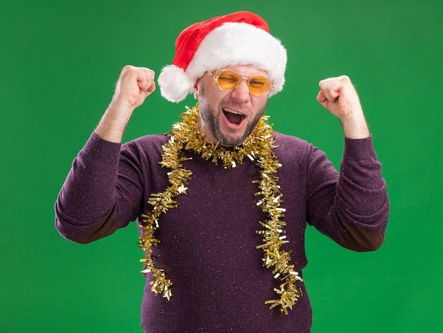 Freudiger mann mittleren alters, der weihnachtsmütze und lametta-girlande um den hals mit brille trägt, die kamera betrachtet, die zwinkert, ja-geste lokalisiert auf grünem hintergrund