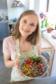 Freudiger nahrungsmittelblogger, der hausgemachtes gemüsegericht präsentiert, in der küche steht, kamera betrachtet und lächelt. vertikaler schuss, hoher winkel. konzept der gesunden ernährung