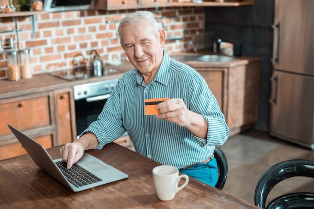 Freudiger netter älterer mann, der eine kreditkarte hält und eine online-zahlung macht, während er seinen laptop benutzt