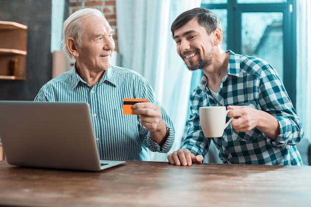 Freudiger positiver junger mann, der lächelt und eine tasse tee hält, während er seinem vater beibringt, eine online-zahlung zu leisten