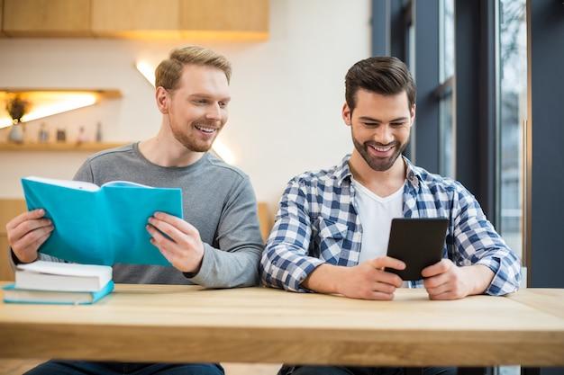 Freudiger positiver netter mann, der zusammen sitzt und lächelt, während er bücher liest