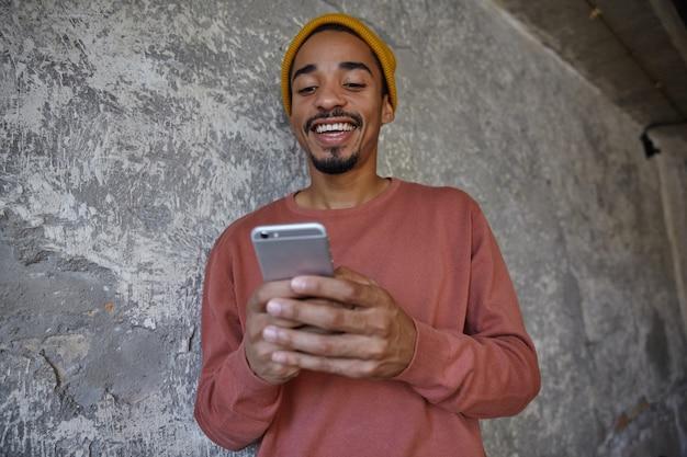 Freudiger schöner braunäugiger junger dunkelhäutiger mann mit bart, der rosa pullover und senfkappe trägt, smartphone in der hand hält und mit seinen freunden plaudert