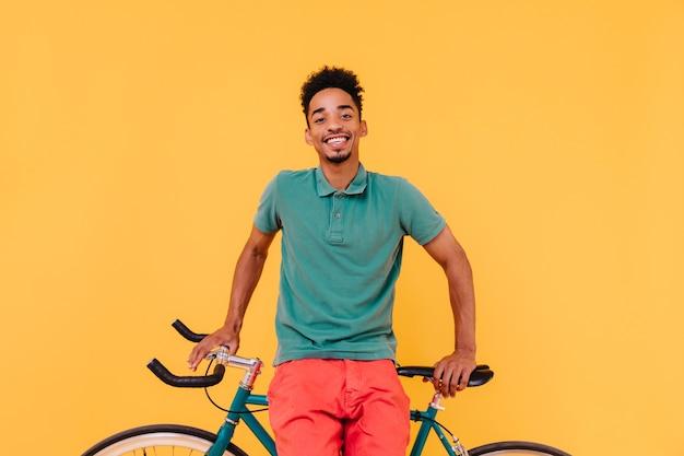 Freudiger schwarzer radfahrer lacht. hübscher afrikanischer junger mann, der mit vergnügen nahe seinem fahrrad aufwirft.