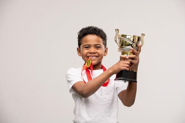 Freudiger süßer gemischter kleiner junge mit medaille und goldener tasse in den händen, die rechts und links mit copyspace stehen