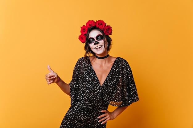 Freudiger süßer mexikaner mit dunklem haar hebt die daumen hoch. porträt des mädchens mit ungewöhnlichem make-up im schönen schwarzen kleid.