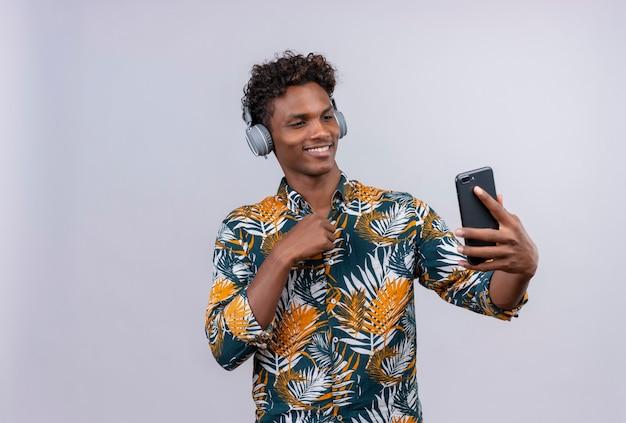 Freudiger und lächelnder junger gutaussehender dunkelhäutiger mann mit lockigem haar im bedruckten hemd der blätter, die kopfhörer tragen, die sein handy auf einem weißen hintergrund betrachten