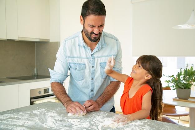 Freudiger vater und tochter, die spaß haben, während teig auf küchentisch kneten, zusammen backen. mädchen, das vätergesicht mit mehlarm berührt. familienkochkonzept