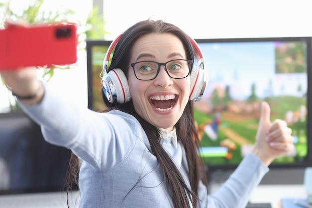 Freudiger weiblicher spieler schießt video auf smartphone auf hintergrund des computerspiels. frauensport