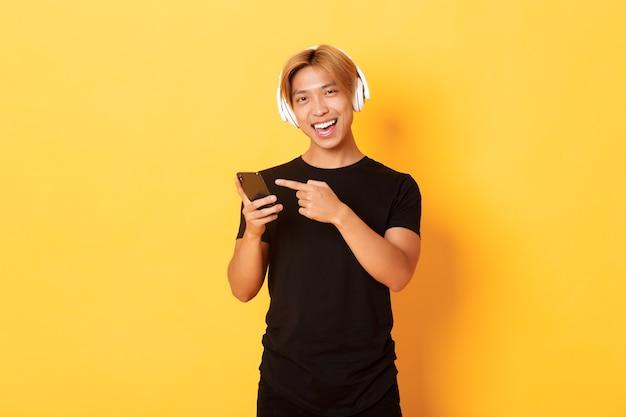 Freudiger zufriedener asiatischer gutaussehender kerl, musik hörend oder guter podcast im kopfhörer, finger auf smartphone mit erfreutem lächeln zeigend, gelbe wand