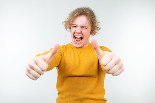 Freudiger zufriedener gewellter blonder junger mann in einem gelben pullover auf einem weißen