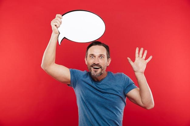 Freudiger zufriedener mann, der leere sprechblase mit kopierraumtext über seinem kopf hält, lokalisiert über rotem hintergrund