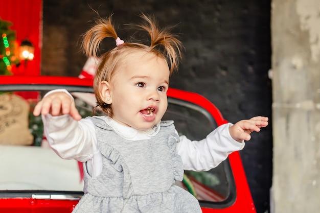 Freudiges baby, das auf rotem weihnachtsauto im wohnzimmer zu hause sitzt