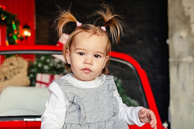 Freudiges baby, das kamera betrachtet, die auf rotem weihnachtsauto im wohnzimmer zu hause frohe weihnachten sitzt