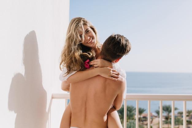 Freudiges blondes mädchen, das ihren freund umarmt und lächelnd rosa blume in der hand hält. junger nackter mann, der seine freundin auf balkon mit meerblick am sonnigen morgen hält.