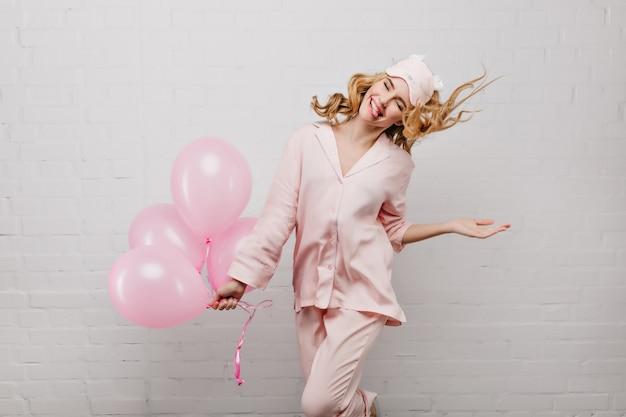 Freudiges blondes mädchen, das mit herausgedrückter zunge aufwirft und bündel rosa luftballons hält. innenporträt der ekstatischen lockigen dame im schlafanzug und in der schlafmaske, die geburtstag feiern.