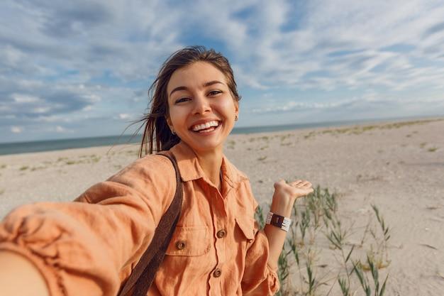 Freudiges brünettes mädchen, das selbstporträt macht und ferien nahe dem ozean genießt. urlaub, tropische stimmung, heiße sommertage.