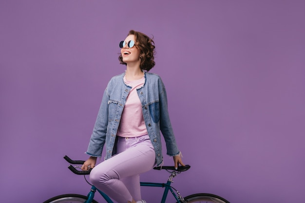 Freudiges brünettes mädchen in der weinlese-jeansjacke stehend. debonair frau in der sonnenbrille, die auf fahrrad aufwirft.