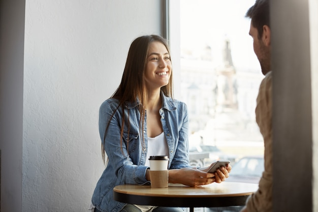 Freudiges dunkelhaariges mädchen in stilvoller kleidung, das in der cafeteria sitzt, kaffee trinkt, lacht und mit freund über arbeit spricht. lifestyle-konzept.