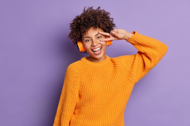 Freudiges, entspanntes, dunkelhäutiges, tausendjähriges mädchen, das eine siegesgeste macht, hört lieblingsmusik in drahtlosen kopfhörern und trägt einen gestrickten orangefarbenen pullover