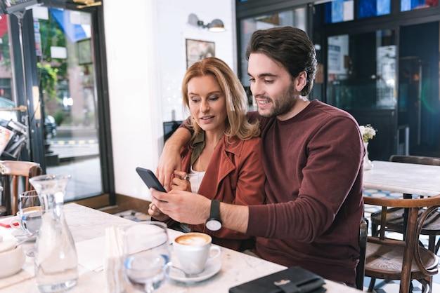 Freudiges erfreutes paar, das im restaurant aufwirft und telefon benutzt