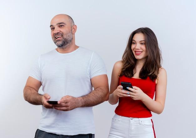 Freudiges erwachsenes paar, das beide handys hält und zur seite schaut