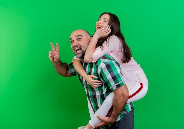 Freudiges erwachsenes paar, das im profilansichtmann steht, der frau auf seinem rücken hält und frau betrachtet, die friedenszeichenfrau tut, die hand unter kinn setzt