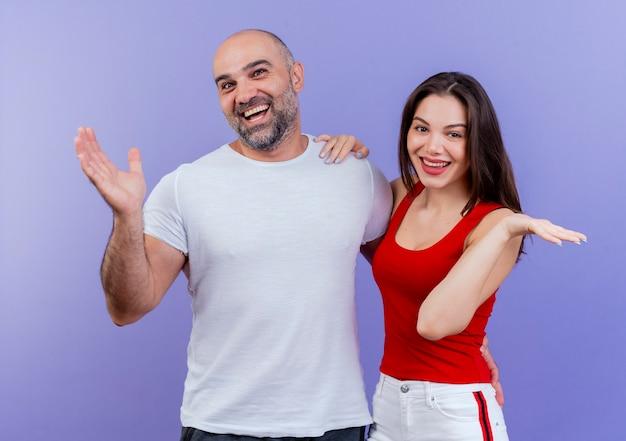 Freudiges erwachsenes paar, das leere hände zeigt
