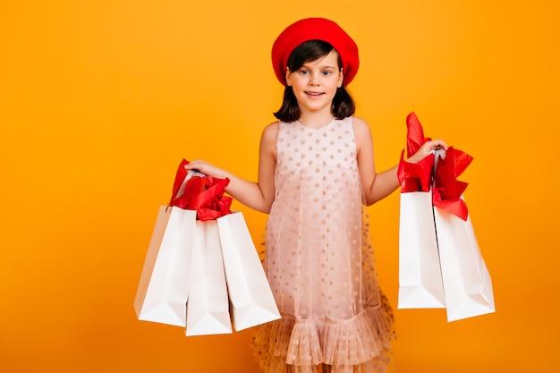 Freudiges französisches kind, das nach dem einkaufen aufwirft. lächelndes kind mit papiertüten.