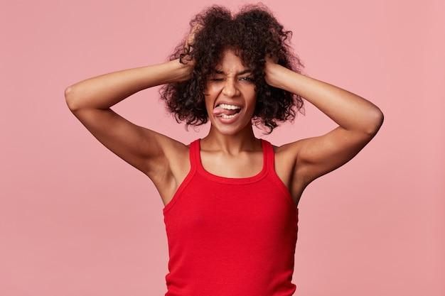 Freudiges freches afroamerikanermädchen mit afro-frisur hält spielerisch ihre hände an ihren kopf, hat spaß, versucht, zwinkert, zeigt zunge, trägt rotes unterhemd, isoliert