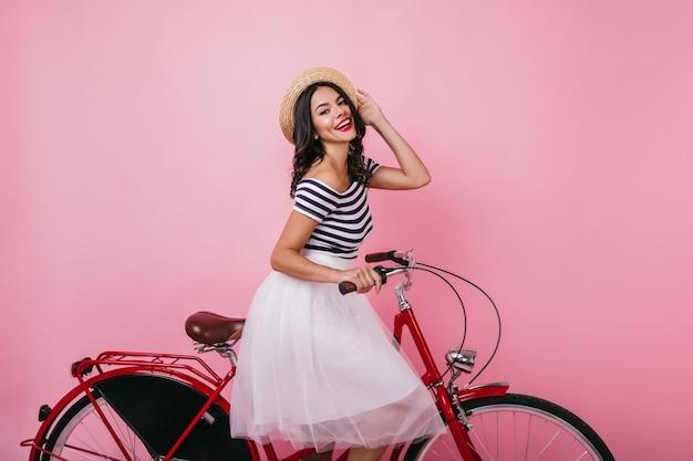 Freudiges gebräuntes mädchen, das auf rotem fahrrad sitzt. innenporträt des ethusiastischen weiblichen modells im rock, der aufwirft und lacht.