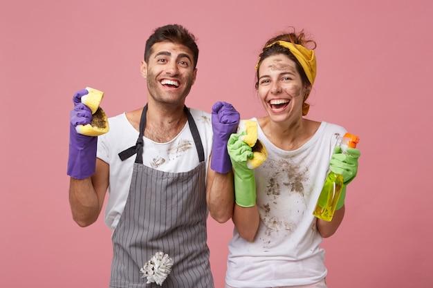 Freudiges, glückliches familienpaar, das vor aufregung die fäuste ballt und froh ist, alle räume seines hauses zu putzen und sich über die ergebnisse zu freuen. erfolgreiche männliche und weibliche arbeiter vom reinigungsdienst