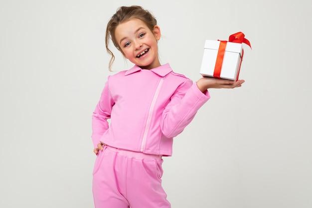 Freudiges glückliches kaukasisches mädchen in einem rosa anzug hält eine schachtel mit einem geschenk mit einem roten band für einen geburtstag auf einer weißen wand