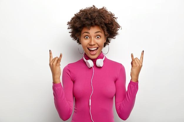 Freudiges hübsches afroamerikanisches mädchen mit lockigem haar, macht rock'n'roll-geste