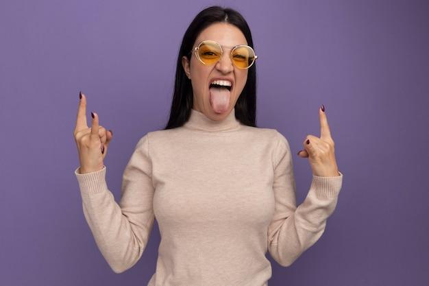 Freudiges hübsches brünettes kaukasisches mädchen in der sonnenbrille streckt zunge heraus und gestikuliert hörner mit zwei händen auf purpur