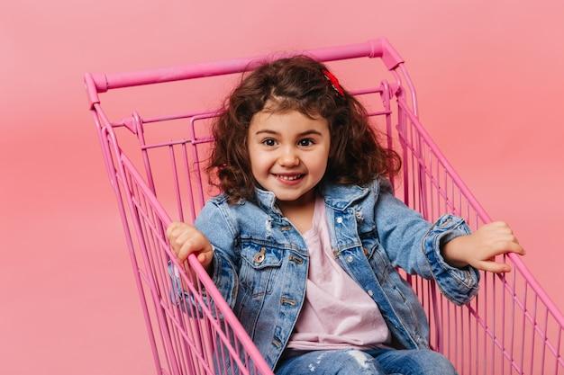 Freudiges jugendliches mädchen, das im einkaufswagen sitzt. studioaufnahme des entzückenden kindes in der jeansjacke.