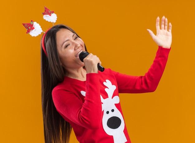Freudiges junges asiatisches mädchen, das weihnachtshaarbügel mit pullover singend auf mikrofon lokalisiert auf orange wand trägt