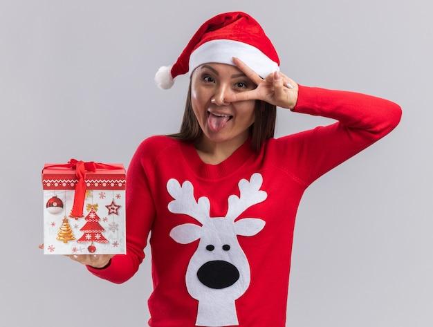 Freudiges junges asiatisches mädchen, das weihnachtshut mit pullover hält, der geschenkbox hält, die friedensgeste und zunge lokalisiert auf weißem hintergrund zeigt