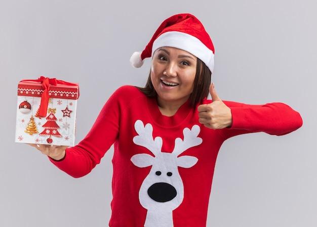 Freudiges junges asiatisches mädchen, das weihnachtsmütze mit pullover hält, der geschenkbox zeigt daumen oben auf weißem hintergrund