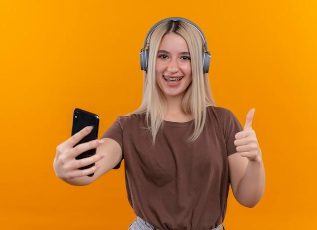 Freudiges junges blondes mädchen, das kopfhörer in zahnspangen trägt, die handy halten und daumen oben auf lokalisiertem orangefarbenem raum zeigen