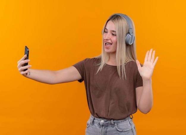 Freudiges junges blondes mädchen, das kopfhörer in zahnspangen trägt, die handy halten und es auf lokalisiertem orangefarbenem raum betrachten und winken