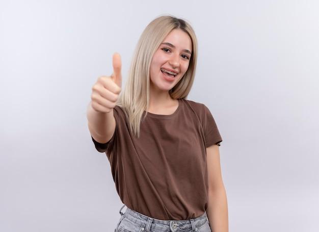 Freudiges junges blondes mädchen in zahnspangen, die daumen oben auf lokalisiertem leerraum mit kopienraum zeigen