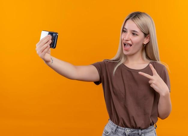 Freudiges junges blondes mädchen in zahnspangen, die friedenszeichen tun und selfie auf lokalisiertem orange raum nehmen